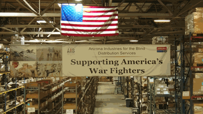 A picture of the AIB DSU Warehouse with racking in the background and a banner in the foreground the reads: Supporting America's War Fighters